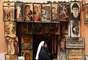 Una religiosa pasa delante de una tienda de recuerdos religiosos muy cerca del Vaticana en dónde mañana Martes comenzará la elección del nuevo pontífice