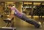 O primeiro exercício é a flexão de braço com os pés no solo ligeiramente afastados e paralelos aos ombros, com as mãos apoiadas em cima da cama. São cinco séries com 20 a 30 repetições. O intervalo entre elas é de 50 segundos