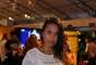 A vendedora Emille Lotze trouxe cor ao visual branco com uma bolsinha de mão amarela, com detalhes em tachas