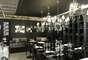 Sala de Jantar com mesa e prateleiras pretas, lustres com vidros e espelhos foi organizada por Maurício Queiroz