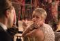 Carey Mulligan em cena com vestido assinado por Miuccia Prada com brilhos e decotes, que passam a fazer parte do figurino feminino da dépoca
