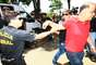 """16 de novembro - Agente da PF impede que Marcos Valério siga antes de outros condenados no julgamento do mensalão ao chegarem ao IML, em Belo Horizonte. A atitude do agente, que possibilitou a chegada de jornalistas à van onde estava Valério, irritou o operador do esquema de corrupção, que chamou o policial de """"incompetente"""""""