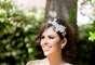 A noiva usa vestido branco da Nikita Nipone com tecido leve, cintura marcada e alça de flores
