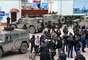 1 de março de 2014 - Pessoas olham para homens não identificados em uniforme militar bloqueando uma base da unidade de guarda fronteira ucraniana em Balaclava