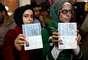 Sírias que moram no Irã mostram seus passaportes enquanto votam para presidente na embaixada da Síria em Teerã, em 28 de maio