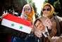 Mulheres sírias exibem a bandeira de seu país junto de uma foto do atual presidente e cadidato Bashar al-Assad, em Teerã, em 28 de maio