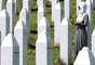 Mulher muçulmana reza em cemitério para vítimas do massacre de Srebrenica, em 11 de julho de 2020