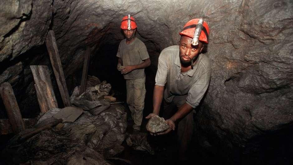 Mineiros cavam as pedras usando cinzéis e enchem sacos com os escombros. Depois, transportam a carga para cima usando uma corda+