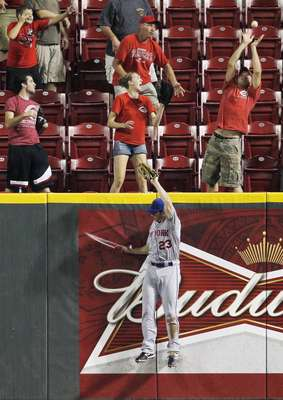 New York Mets' right fielder Mike Baxter can't make the catch on a home run ball off the bat of Cincinnati Reds Ryan Ludwick.
