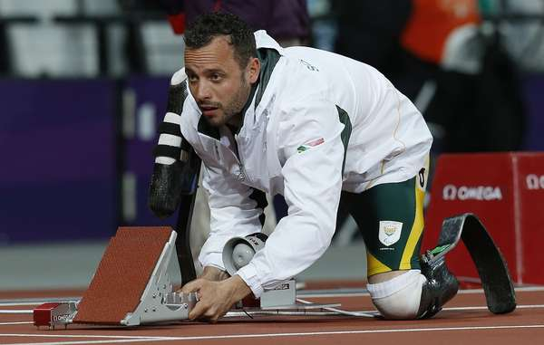Oscar Pistorius of South Africa adjusts the starting blocks before his men's 200m T44 classification heat at the Olympic Stadium.