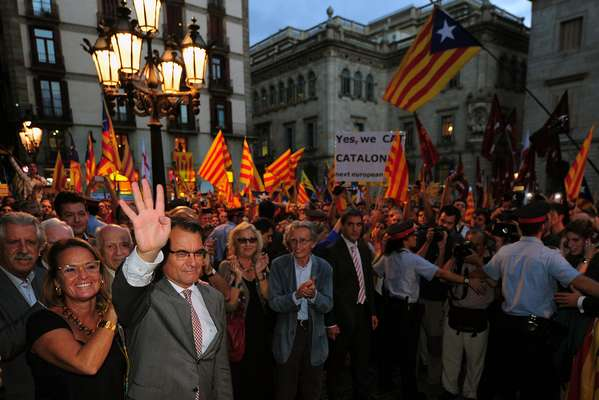 El presidente catalán Artur Mas y su mujer Elena Rakosnic son recibidos por una multitud en la Plaza Sant Jaume de Barcelona.