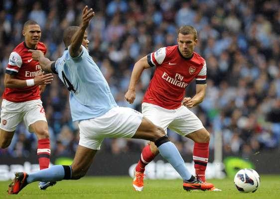 Manchester City's Vincent Kompany (C) challenges Arsenal's Lukas Podolski (R).