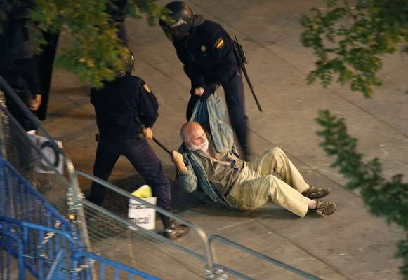 Dos policías arrastran por el suelo a un hombre de avanzada edad muy cerca del Congreso de los Diputados.