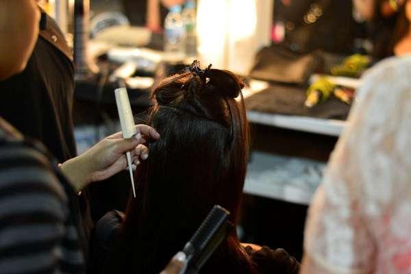 Modelo da grife Espaço Fashion passa por cabeleireiro antes do desfile desta quinta-feira (8)