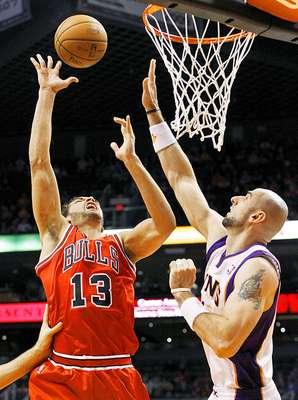 Bulls vs. Suns: Joakim Noah (13) saca un disparo ante la marca de Marcin Gortat. Chicago tuvo que emplearse en tiempo extra para vencer 112-106 a Phoenix en el US Airways Center.