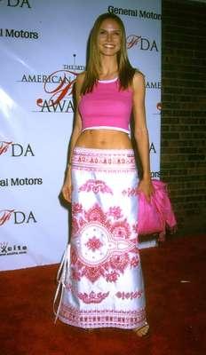 Heidi Klum es una de las modelos más famosas del mundo de la moda. Su forma de vestir siempre ha sido blanco de múltiples opiniones por parte de los grandes modistos. Esta es su transformación de imagen. En la foto la vemos en 1999 con un conjunto de dos piezas en color rosa un poco inadecuado para la alfombra roja, aunque demostraba su bien torneado cuerpo.