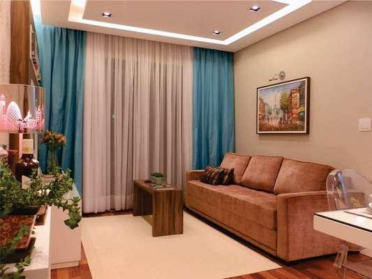Na sala, o uso de poucos móveis, e todos encostados nas paredes, ajudou a aumentar a área de circulação da casa. No detalhe, o sofá cama moderno e despojado