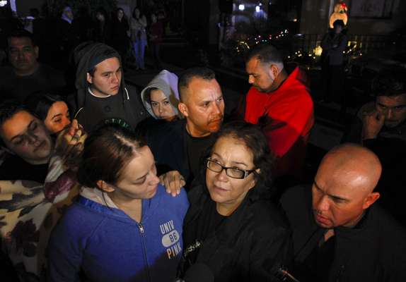 Jenni Rivera's family members gathered outside their mother's home, last night.  Jenni's sister, Rosie (in the blue hoodie),  hugs her mother Rosa Rivera, while Pastor Pedro Rivera Jr., rear, and Gustavo Rivera, right, watch.