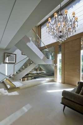 No hall de entrada, o pé-direito duplo valoriza o imponente lustre de cristal. Piso de mármore e guarda-corpo em vidro reforçam o visual sofisticado