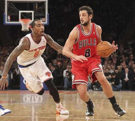 Marco Belinelli de los Chicago Bulls, mueve el balón ante la marca de R. Smith
