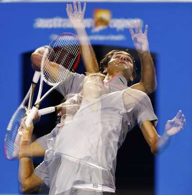 Roger Federer of Switzerland serves to Bernard Tomic of Australia in their men's singles match at the Australian Open tennis tournament in Melbourne January 19, 2013. Picture taken using multiple exposures. REUTERS/Daniel Munoz (AUSTRALIA - Tags: SPORT TENNIS)