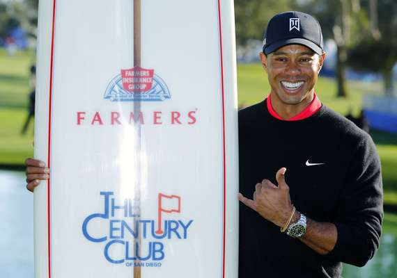 U.S. golfer Tiger Woods poses with a surf board as one of his prizes after winning the Farmers Insurance Open in San Diego, California January 28, 2013. Woods withstood a late bogey, double-bogey, par, bogey wobble in strengthening winds to clinch his 75th PGA Tour title by four shots at the fog-delayed Farmers Insurance Open on Monday.