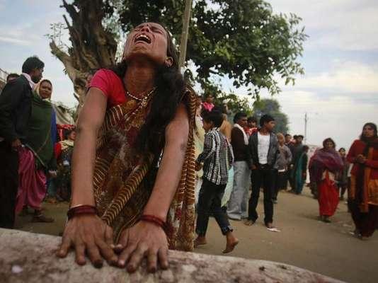 """Devotos hindúes que creen estar poseídos por espíritus malignos dan gritos y quedan en estado de trance en el templo de Guru Maharaj Deoji en Maljpur, India. Esta ciudad en el estado de Madhya Pradesh celebra una feria en la que da la bienvenida a gente de todas partes de la India para que sean exorcizados. Los supuestos poseídos, generalmente, son mujeres traídas por parientes. El ritual indica que la persona que será exorcizada debe dar vueltas corriendo alrededor del jardín del templo para confundir al """"fantasma"""" y luego deben ser golpeados con una escoba para debilitar al espíritu maligno."""