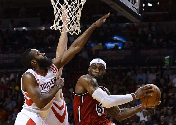 Miami Heat's LeBron James (R) is defended by Houston Rockets' Cole Aldrich (C, obscured) and James Harden (L) during the first half of their NBA basketball game in Miami, Florida, February 6, 2013.