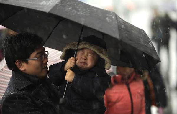 Un niño en brazos de su padre llora bajo la nieve de Shanghai mientras se dirigen a coger el tren, que usarán millones de personas estos días, para volver a los lugares de origen por el año nuevo chino.
