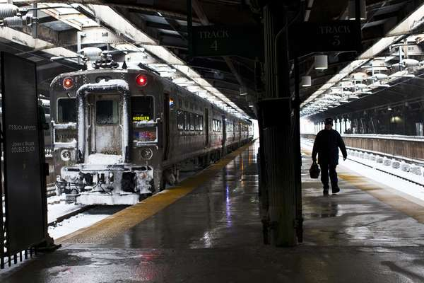 A NJ transit worker arrives to Hoboken station after the passing of a winter storm in Hoboken, New Jersey, February 9, 2013. A blizzard packing hurricane-force winds pummelled the northeastern United States on Saturday, killing at least one person, leaving about 600,000 customers without power and disrupting thousands of flights. REUTERS/Eduardo Munoz (UNITED STATES - Tags: ENVIRONMENT DISASTER)
