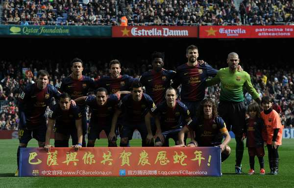 Barcelona team pose with the sign 'Happy New Year!' in Chinese.