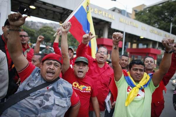 Simpatizantes do presidente venezuelano, Hugo Chávez, saúdam a chegada dele ao país em frente a hospital militar de Caracas. Chávez retornou de surpresa de Cuba nesta segunda-feira. Ele seguirá o tratamento ao cancêr no hospital militar