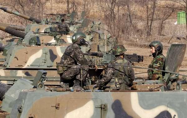 """Soldados sul-coreanos conversam em cima de tanque durante exercício militar conjunto entre tropas de seu país e dos Estados Unidos em Paju, nas proximidades da fronteira com a Coreia do Norte. Os dois países iniciaram o evento anual nesta segunda-feira, mesmo dia em que a Coreia do Norte declarou """"completamente nulo"""" o armistício que pôs fim à Guerra da Coreia (1950-53) e garantiu que está se preparando para uma guerra iminente contra a Coreia do Sul e os Estados Unidos"""