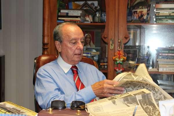 Jair Soares folheia jornal da época com a manchete de sua eleição