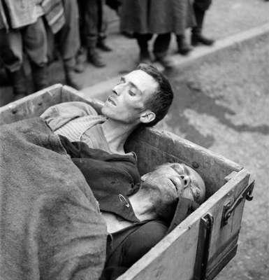"""Dois prisioneiros mortos são transportados após a libertação do campo de concentração de Dachau, nas proximidades de Munique, Alemanha, em 1945.O campo de concentração de Dachau abriu em 22 de março de 1933, apenas 51 dias após Adolf Hitler se tornar chanceler alemão. Dachau foi o primeiro campo para """"prisioneiros políticos"""" mantidos pela SS e se tornou em um modelo para os demais campos controlados pela polícia de elite de Hitler. O local permaneceu aberto até 1945, quando foi libertado por tropas americanas. Cerca de 200 mil pessoas de 38 diferentes nacionalidades foram detidas em Dachau e estima-se que 41,5 morreram ali"""