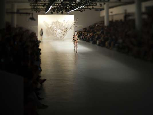 Na passarela, uma enorme escultura transparente de rabo de sereia durante o desfile da Amapô