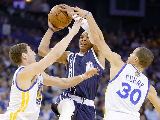 Thunder vs. Warriors: Russell Westbrook (0) intenta un disparo a la canasta ante la marca de Klay Thompson y Stephen Curry (30).