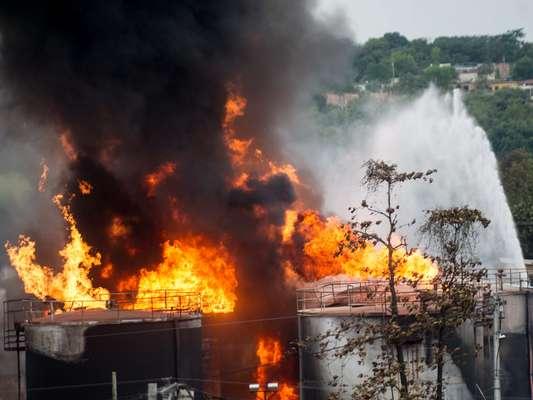 23 de maio - Bombeiros trabalham no combate às chamas em depósito de combustíveis