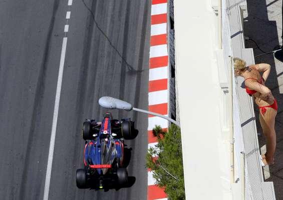 Mulher observa a passagem de Jenson Button pelo circuito urbano de Monte Carlo, no primeiro dia de treinos para o GP de Mônaco