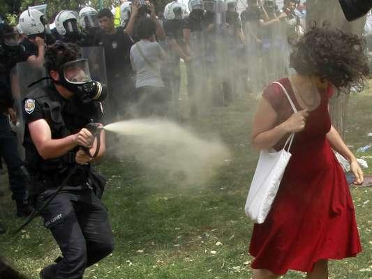 Policial borrifa gás lacrimogêneo na direção da mulher do vestido vermelho durante protesto contra a destruição de árvores na Praça Taksim, em Istambul, em 28 de maio. Imagens da mulher feitas pelo fotógrafo Osman Orsal foram compartilhadas viralmente nas redes sociais e se tornaram símbolo dos recentes protestos na Turquia
