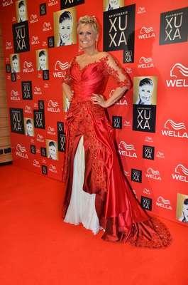"""Em sua festa de comemoração de 50 anos, Xuxa apareceu com um vestido vermelho com a saia de baixo branca. O vermelho era a cor pedida para festa, tanto que as demais convidadas também a usaram, mas a Rainha dos Baixinhos, apesar das cinco décadas de vida, parece que não quer sair do mundo da fantasia. O vestido feito por Samuel Cirnansck mais parecia de uma """"rainha má"""", saída dos contos de fada onde sempre há bruxas"""