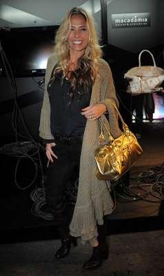 Adriane Galisteu usou calça skinny com botas de cano longo, camisa preta e longo casaco de tricô bege. Para contrastar com os materiais opacos, a bolsa dourada foi boa opção