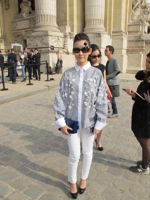 Mulher usa camisa azul com aplicações de flores, calça comprida, óculos com a silhueta da Chanel e bolsa Boy Lego Brick