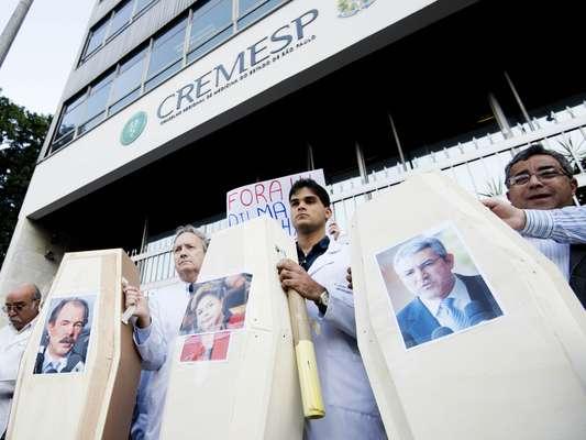 Manifestantes mostram fotos dos ministros Aloizio Mercadante (esq.), da Educação, e Alexandre Padilha, da Saúde, e da presidente Dilma Rousseff em caixões durante protesto em São Paulo