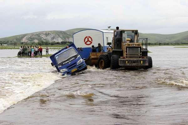 Trabalhadores tentam resgatar caminhão que foi arrastada pela água durante inundação em Hulun Buir, na região chinesa de Mongólia Interior. A enchente foi provocada pela passagem do tufão Soulik, que já deixou mais de 200 mortos na China desde a última sexta-feira