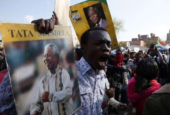Sul-africanos cantam e dançam durante a celebração do 95º aniversário de Nelson Mandela em frente ao hospital em que ele está internado, em Pretória. Herói da luta contra o apartheid, Mandela está hospitalizado desde o último dia 8 de junho por causa da recaída de uma infecção pulmonar, mas a presidência do país diz que ele está melhorando constantemente. Seu aniversário é celebrado por milhões de pessoas no país