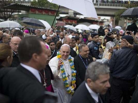 Papa Francisco recebe colar de flores nas cores do Brasil ao chegar à comunidade de Varginha, no Complexo de Manguinhos, no Rio, na quinta-feira