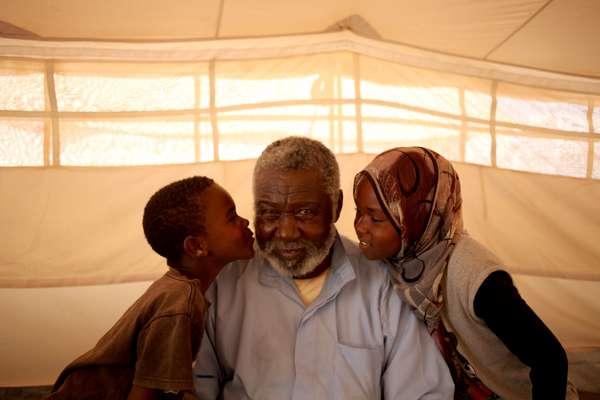 """Mohammed Abdullah, 75 anos, recebe beijo dos seus netos Rashed, 7 anos, e Afrah, 11 anos. """"Eu sonho em ter um país para os seus entes queridos, um país seguro, sem humilhação, um país que que nós sempre quisemos e um país pelo qual nosso povo já derramou muito sangue"""