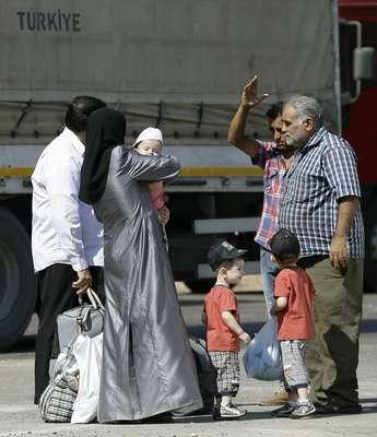 Refugiados sírios passam pela fronteira e entram em território turco para fugir da guerra