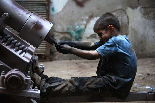 Há dois anos, a guerra civil na Síria muda a vida de milhões de pessoas no país. Para 2 milhões de pessoas, a saída foi deixar o país e tentar a sorte como refugiados para além de suas fronteiras. Para Issa, 10 anos, signficou o fim da infância. Antes mesmo de entrar na adolescência, o menino trabalha 10 horas por dia, seis dais por semana, ajudando o seu pai em uma fábrica de armas do Exército Livre Sírio - principal organização rebelde armada do país -, em Aleppo. Seu único dia de folga é sexta-feira, dia em que os muçulmanos reservam para orações. No dia 7 de setembro, a rotina do menino foi registrada em um ensaio fotográfico feito por Hamid Khatib, da agência Reuters